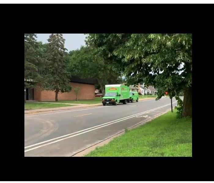 open street with a green servpro van