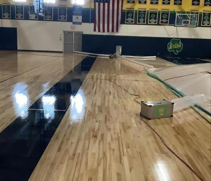 high school gym floor with air being blown into the plastic covering