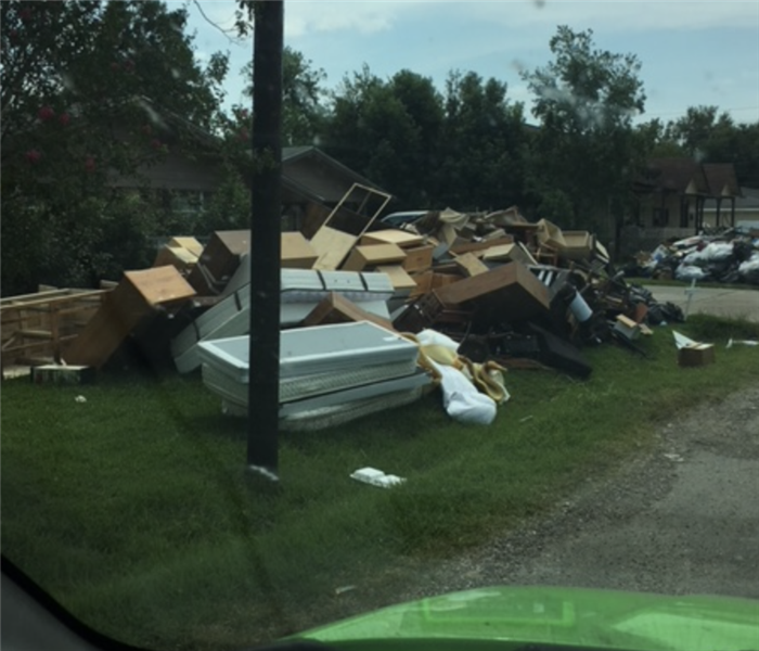 damaged building materials and mattresses on front lawn