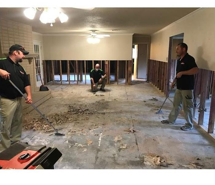 three workers cleaning up a damaged floor